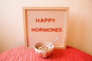 A Happy Hormones sign with a bowl of cereal in front